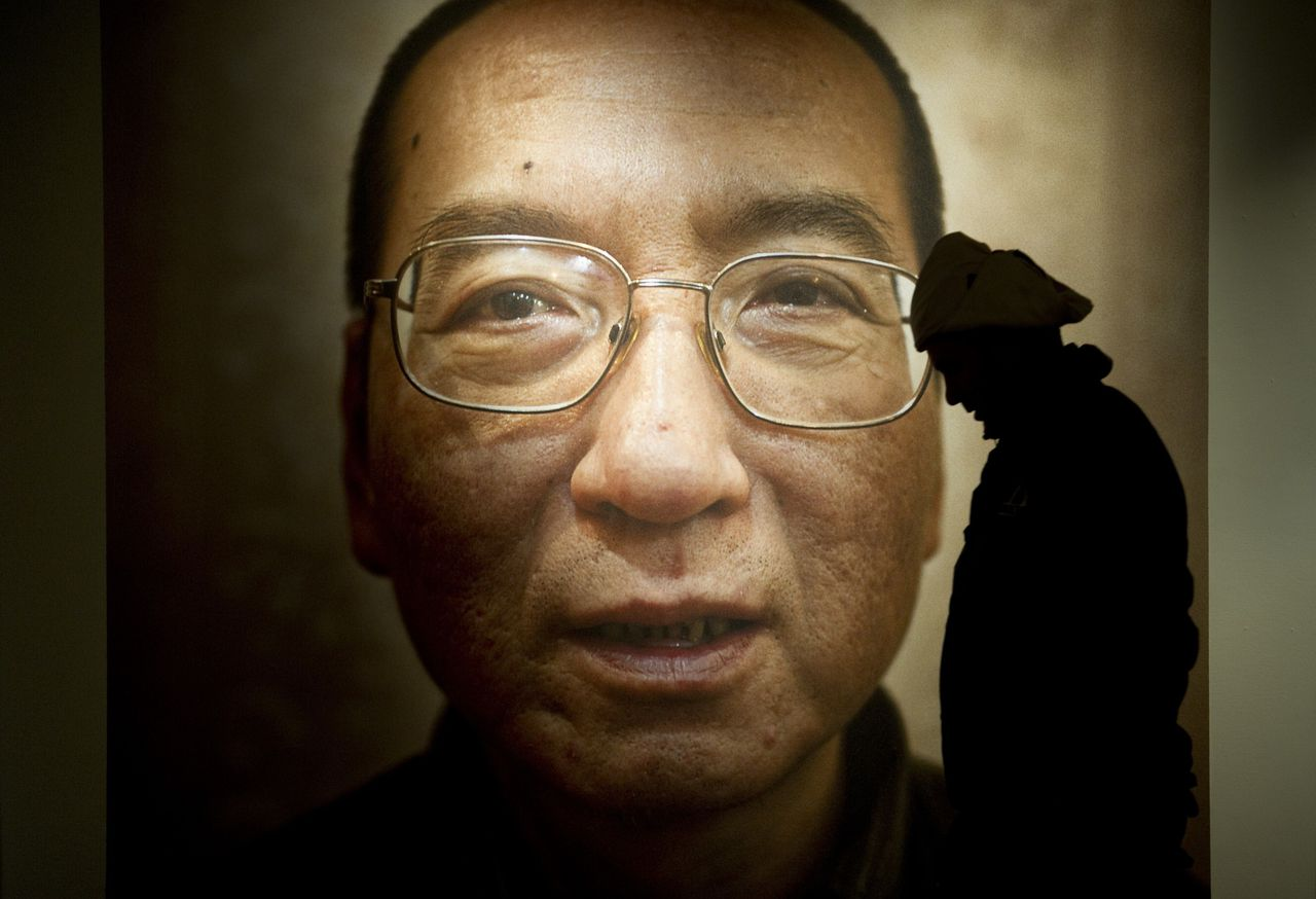 A man walks in front of a poster of Chinese dissident and peace prize laureate Liu Xiaobo at an exhibition at the Nobel Peace Center in Oslo, December 9, 2010. With the guest of honour stuck in a Chinese prison, this year's Nobel Peace Prize ceremony will centre around an empty chair, as its celebration of dissident Liu Xiaobo continues to split the global community and infuriate Beijing. The Norwegian Nobel Committee head said he was surprised at the level of international support for jailed Chinese dissident and peace prize laureate Liu Xiaobo despite pressure from Beijing. AFP PHOTO/ODD ANDERSEN