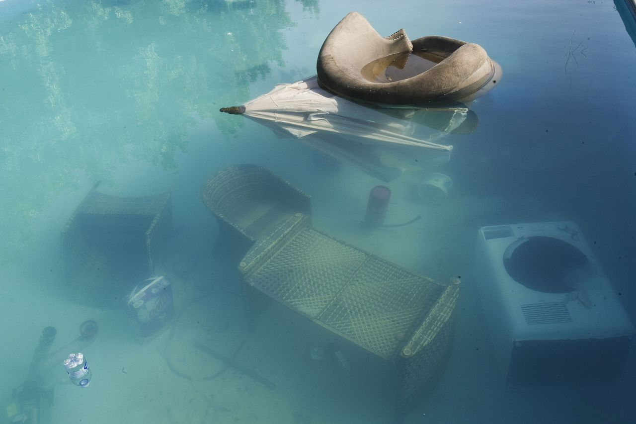An armchair and parasol float in the swimming pool of the US consulate in Benghazi on September 13, 2012, following an attack on the building late on September 11 in which the US ambassador to Libya and three other US nationals were killed. Libya said it has made arrests and opened a probe into the attack, amid speculation that Al-Qaeda rather than a frenzied mob was to blame. AFP PHOTO/GIANLUIGI GUERCIA