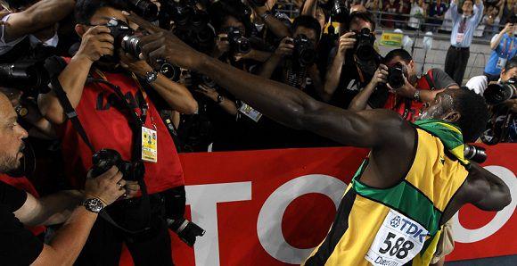 Caption: Jamaica's Usain Bolt celebrates winning the men's 200 metres final at the International Association of Athletics Federations (IAAF) World Championships in Daegu on September 3, 2011. AFP PHOTO / ADRIAN DENNIS