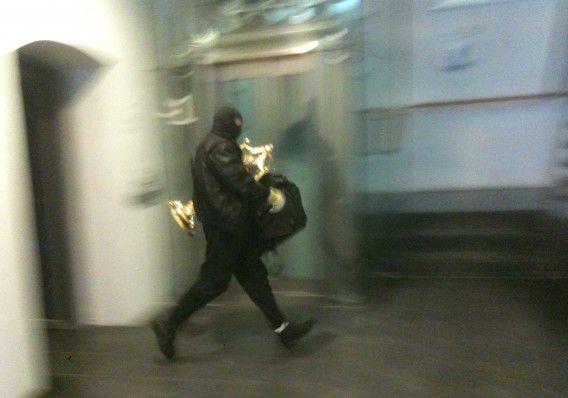 Een van de daders loopt met de gestolen voorwerpen in het museum Catharijneconvent.