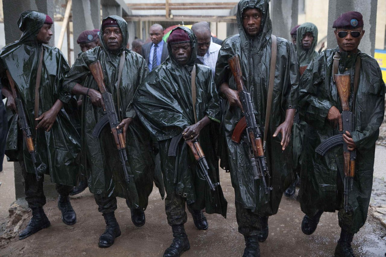 Members of Congo's presidential guard walk through heavy rain ahead of incumbent Joseph Kabila (not seen) as he leaves a polling station after voting in Democratic Republic of Congo's capital Kinshasa, November 28, 2011. Voting began slowly on Monday in Congo's second-post war election, held despite fears logistical problems and irregularities would undermine the result. REUTERS/Finbarr O'Reilly (DEMOCRATIC REPUBLIC CONGO - Tags: POLITICS ELECTIONS MILITARY TPX IMAGES OF THE DAY)