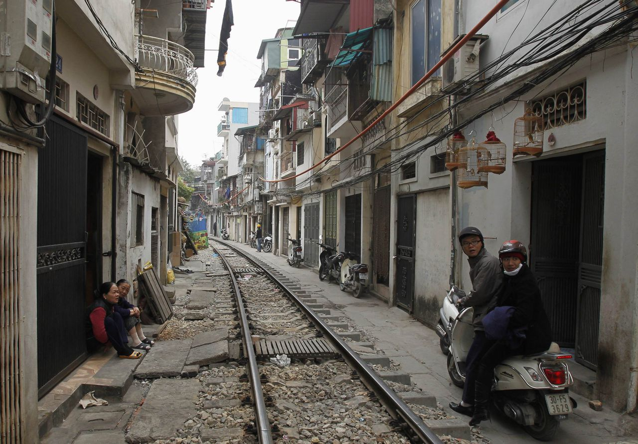 Residents (L) sit in front of houses as a couple rides a scooter along the railway track in downtown Hanoi December 27, 2011. The Kham Thien railway hamlet, a 200-meter (656-ft) stretch of residences along the railway track in center Hanoi, is one of most dangerous traffic problems in the country. Despite the many accidents and deaths every year and warnings from authorities, people continue to live and make their livelihoods near the track. REUTERS/Kham (VIETNAM - Tags: SOCIETY TRANSPORT)