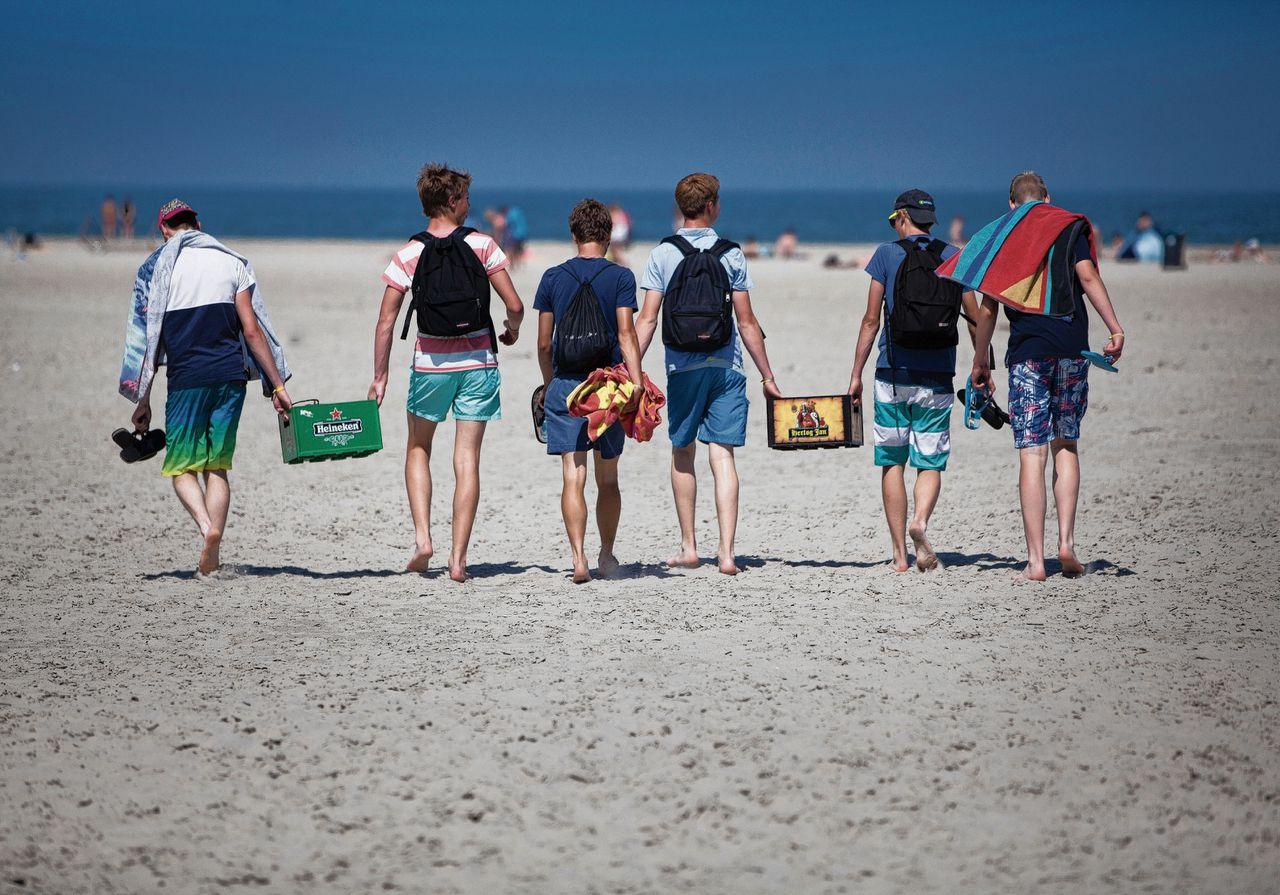 Jongeren met kratten bier onderweg naar het strand bij Formerum. De meeste minderjarige campinggasten noemen het geen enkel probleem om alcohol te drinken op Terschelling.