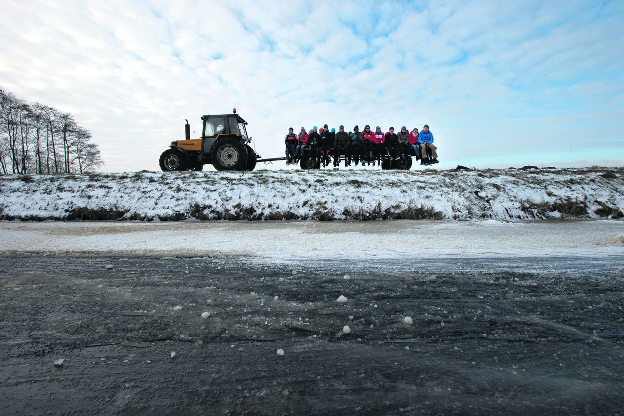 Participants of the Five Lakes Skating Tour are being transported on a tractor to avoid a stretch of bad ice in Wanneperveen, near Giethoorn, northern Netherlands, Thursday Jan. 24, 2013. Some 15,000 skating enthusiasts participated in the first tour on natural ice, but a stretch of rapidly deteriorating ice in Wanneperveen forced organizers to call off the tour after a few hours. Dutch police later stopped people from reaching the area. (AP Photo/Peter Dejong)