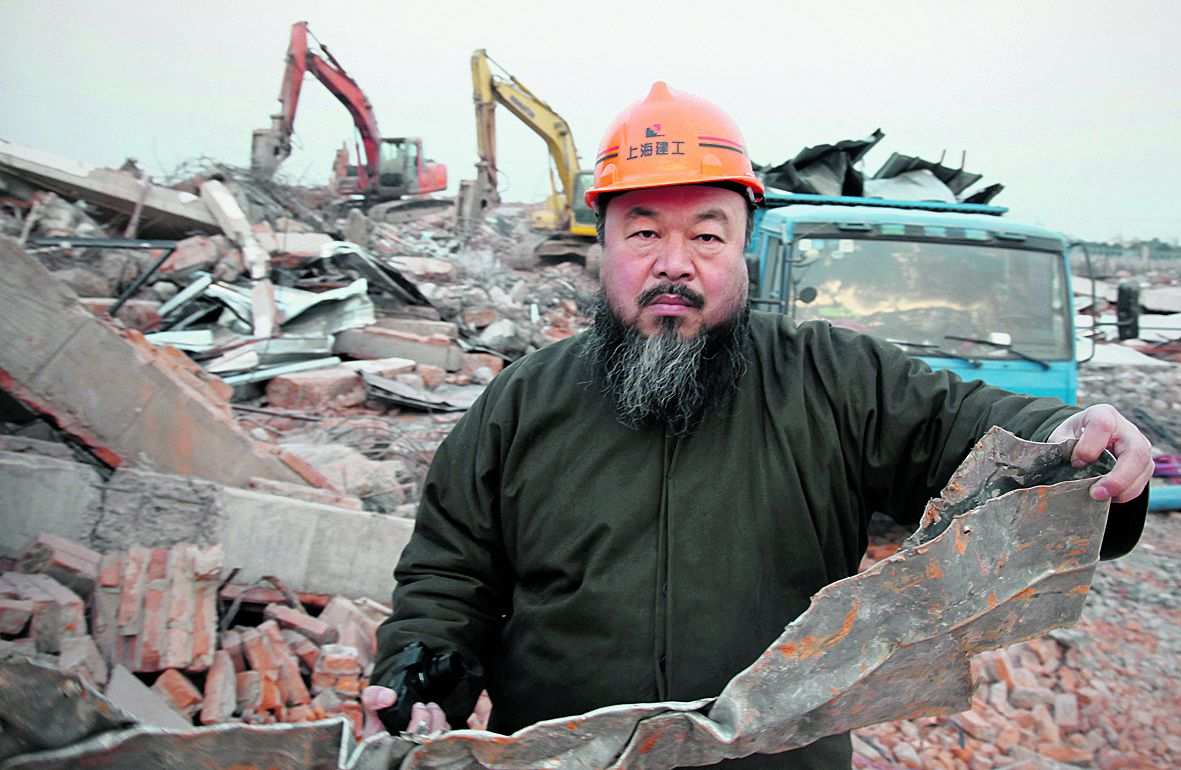 This picture taken in suburban Shanghai on January 11, 2011 shows Chinese artist Ai Weiwei holding a piece of debris of his newly built Shanghai studio after it was demolished. The 53-year-old Ai, one of China's most famous and controversial artists, said the demolition which began before dawn without any prior notification was linked to his political activism. AFP PHOTO