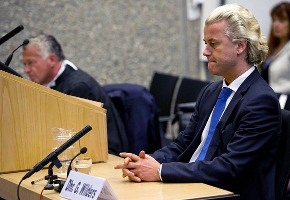 """Dutch anti-Islam politician Geert Wilders, right, and his lawyer Bram Moszkowicz, left, are seen inside the courtroom in Amsterdam, Netherlands, Monday, May 23, 2011. Judges in the Netherlands have ruled that an anti-Islam lawmaker's hate speech case can continue, rejecting claims by his lawyer that the court trying him was not impartial. Wilders is on trial on charges of """"making statements insulting to Muslims as a group,"""" and inciting hatred against Muslims. (AP Photo/ Marcel Antonisse Pool)"""