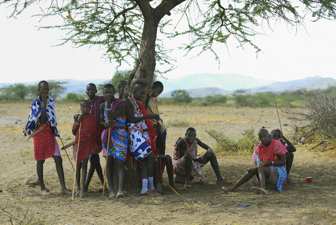 Maasai men wait for a traditional wedding ceremony in Olepolos village, 120 km (74 miles) southeast of Nairobi, March 31, 2007. In the Maasai tradition the groom has to pay for his bride in cows and sheep, which have to be brought to her family on the wedding day. REUTERS/Damien Guerchois (KENYA)