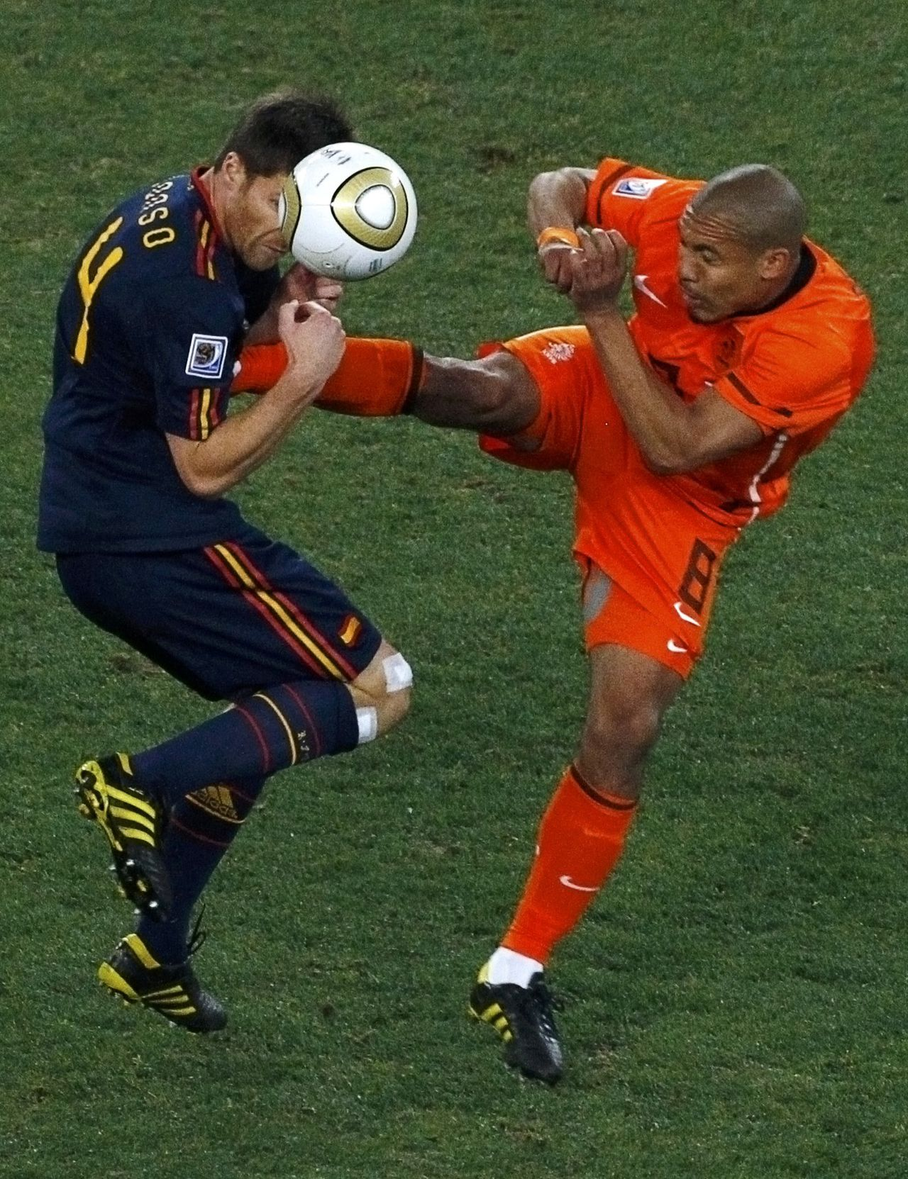 Spain's Xabi Alonso (L) gets a boot in his chest by Netherlands' Nigel de Jong as they fight for the ball during their 2010 World Cup final soccer match at Soccer City stadium in Johannesburg July 11, 2010. REUTERS/David Gray (SOUTH AFRICA - Tags: SPORT SOCCER WORLD CUP IMAGE OF THE DAY TOP PICTURE)