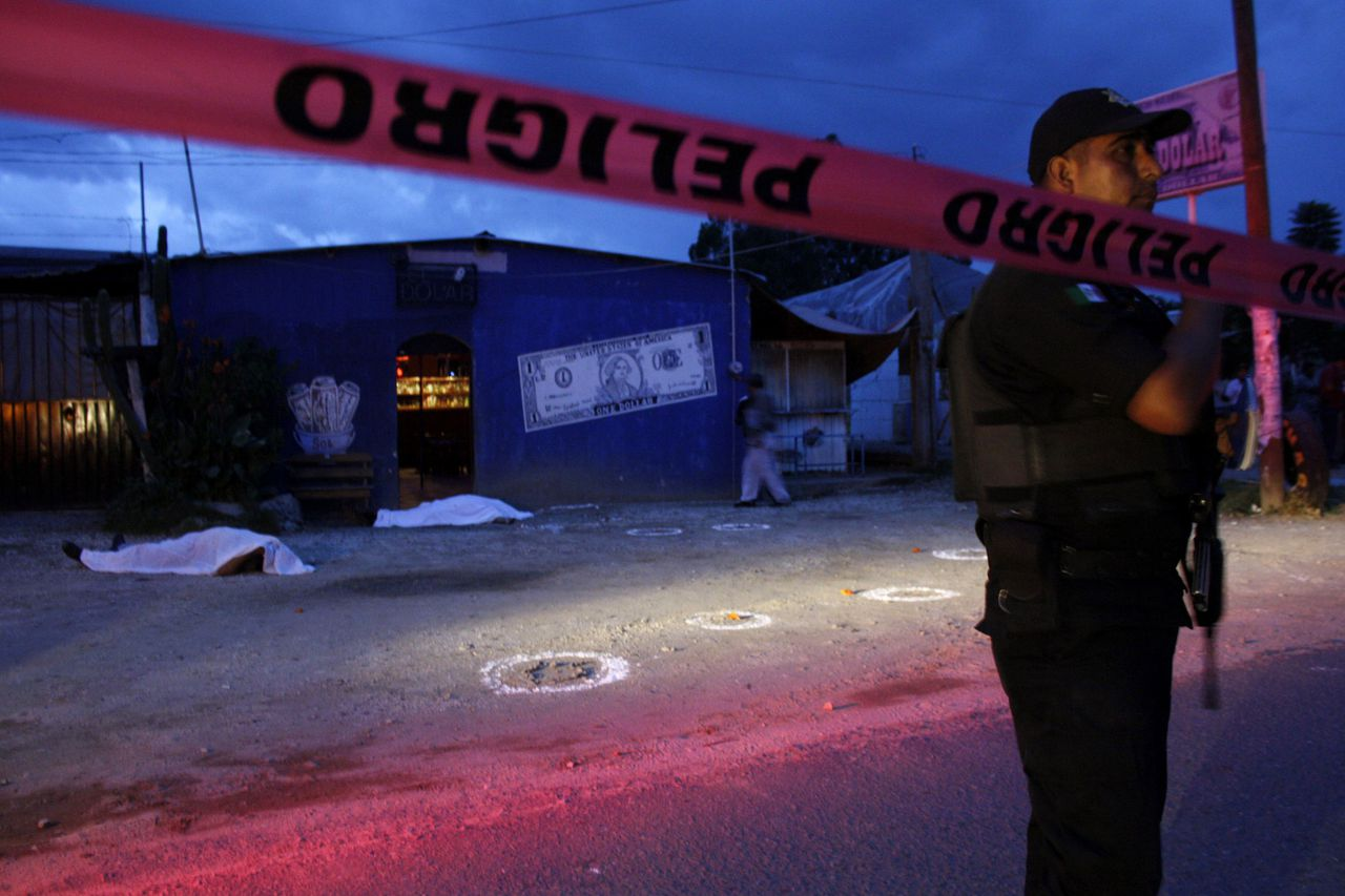 "A police officer stands behind a police line at a crime scene where two men were shot dead outside a bar called ""The Dollar"" in Oaxaca September 28, 2011. The owner of the bar and his bodyguard were shot dead by three hitmen, according to local media. REUTERS/Jorge Luis Plata (MEXICO - Tags: CRIME LAW CIVIL UNREST)"