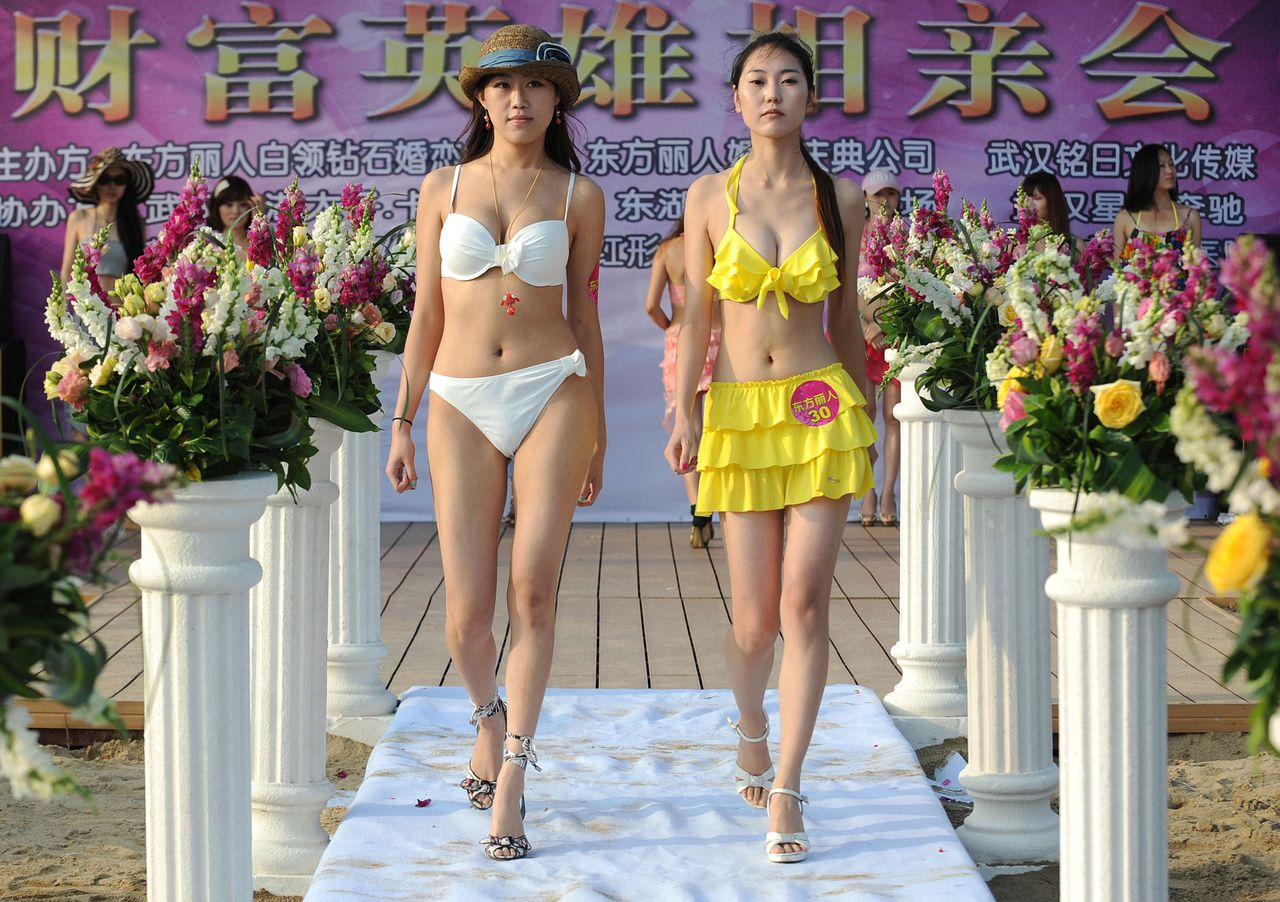 This photo taken on June 25, 2011 shows a group of Chinese women parading in their bikinis during a matchmaking event for wealthy men, with assets over 30 million yuan or make over one million yuan in annual income, and must also pay 99,999 yuan for the entrance ticket, held at the East Lake beach in Wuhan, central China's Hubei province. China's wealthiest are getting richer, with the minimum amount needed to make the top 400 rising to 425 million USD from 300 million in 2010. CHINA OUT AFP PHOTO