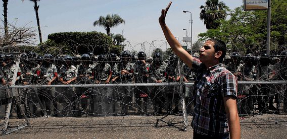 Name: fd9aa3d41542370c0e0f6a706700ad30.jpg Caption: An Egyptian protester directs his fellow protesters away from the army security barrier blocking the road leading to the Ministry of Defense, in Cairo, Egypt Sunday, April 29, 2012. Assailants attacked demonstrators gathered outside the Defense Ministry in Egypt's capital to call for an end to military rule with rocks and firebombs, killing one protester and wounding scores, security officials said on Sunday. (AP Photo/Nasser Nasser) IPTC Date: 05:16 29/04/12