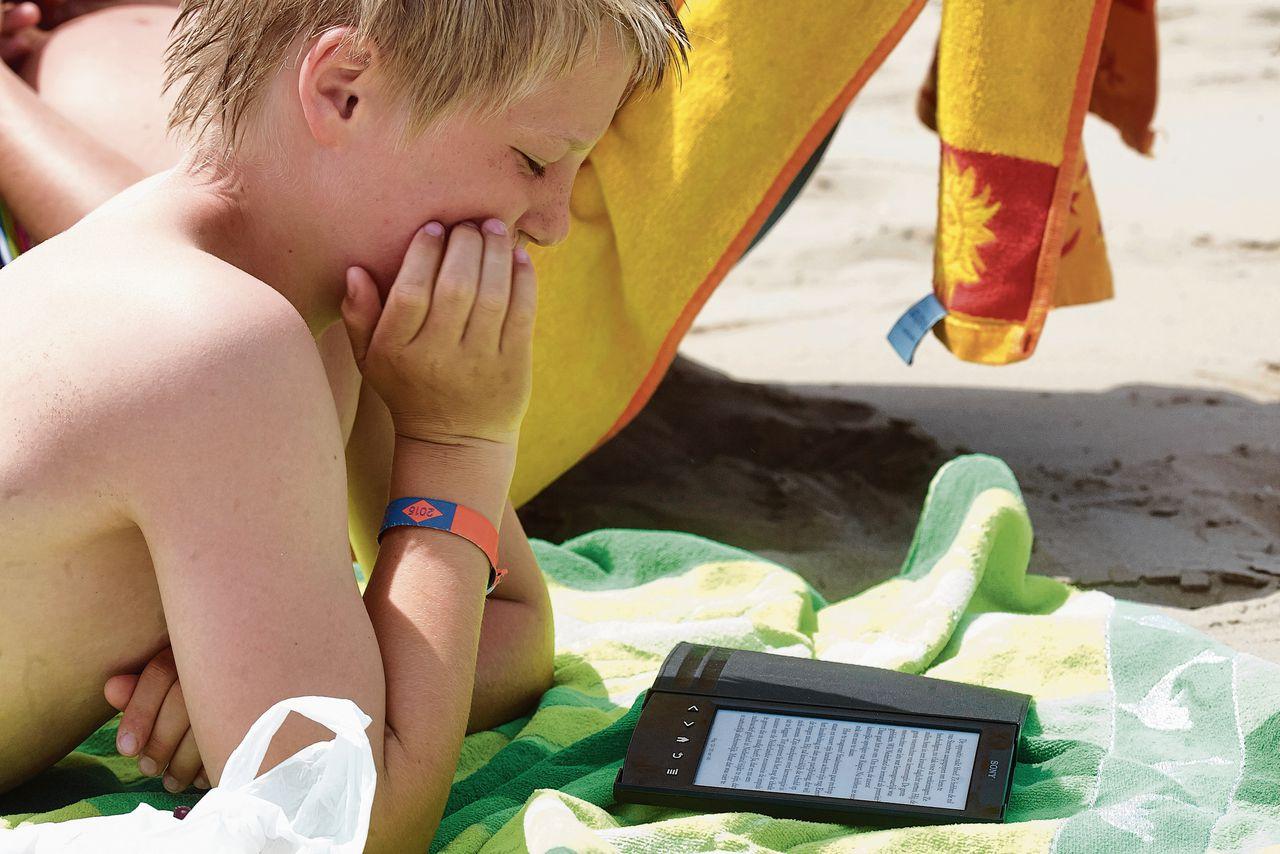 Een Nederlands jongetje leest aan het strand in Venetië.