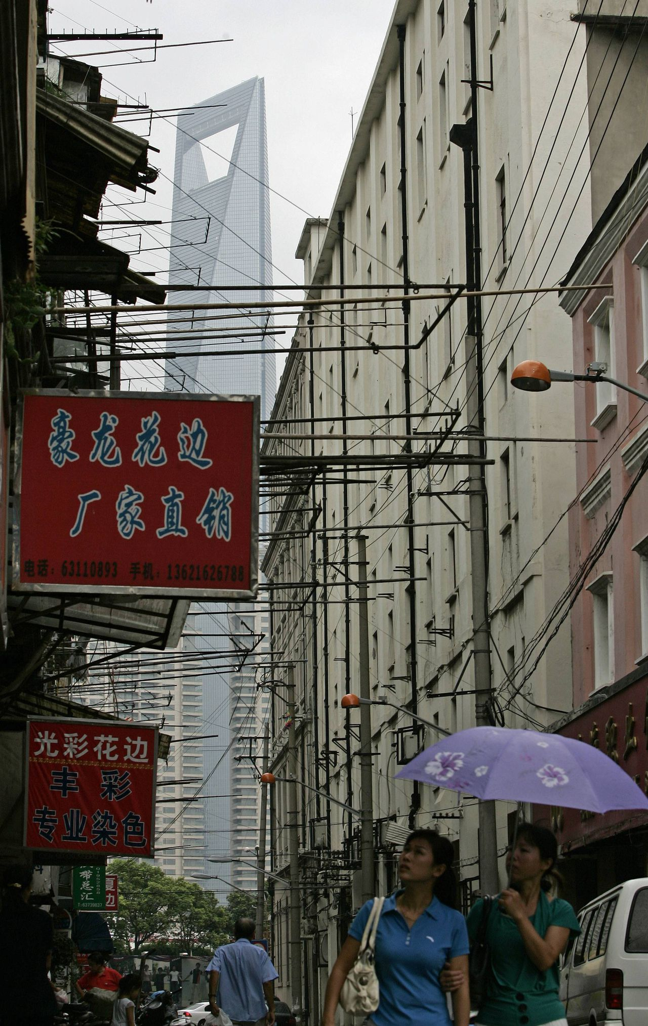 Shanghai World Financial Centre building in seen in the background as two women walk down an old alley, August 29, 2008. China's tallest building, the 492-metre (1,614-ft) Shanghai World Financial Centre, is on track to reach 90 percent occupancy within a year despite worries over the economy, its developer and top shareholder said on Thursday. REUTERS/Aly Song (CHINA)