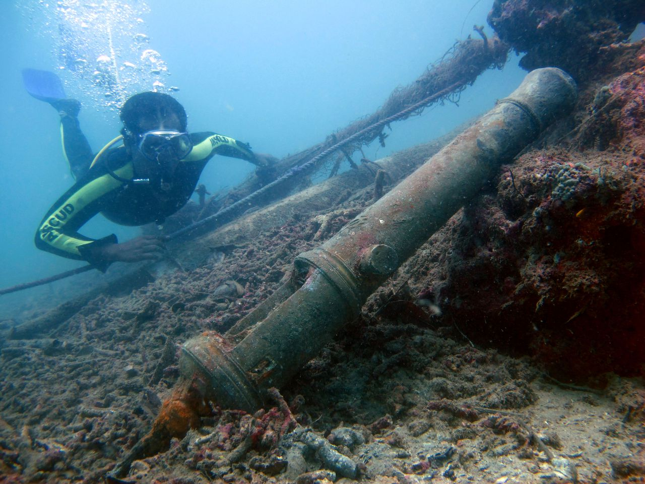 In this Monday, Feb. 13, 2012 photo, a diver swims near a Dutch East India Company (VOC) cannon from a shipwreck that is believed to be from the 17th century, in Mentawai Islands, Indonesia. Indonesia, a sprawling archipelago nation straddling the equator, remains desperately poor despite its vast oil, coal and gold reserves. Its graveyard of ships from Asia, Europe and the Middle East, one of the biggest in the world with nearly 500 wrecks identified so far, has long been viewed as yet another resource to exploit. (AP Photo/Dita Alangkara)