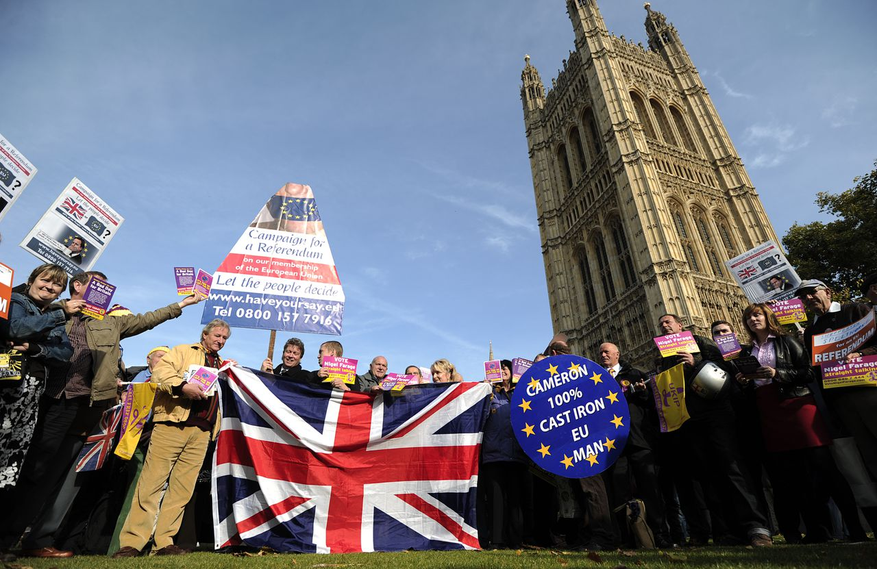 United Kingdom Independence Party (UKIP) supporters hold Union Jack flags and placards as they take part in a demonstration outside the Houses of Parliament in central London on October 24, 2011, the day that Parliament votes on whether to hold a referendum on the UK's membership of the European Union. David Cameron faced the biggest rebellion of his premiership today as eurosceptic backbenchers in his Conservative Party vowed to defy orders and vote for a referendum on Britain's EU membership. AFP PHOTO/ CARL COURT