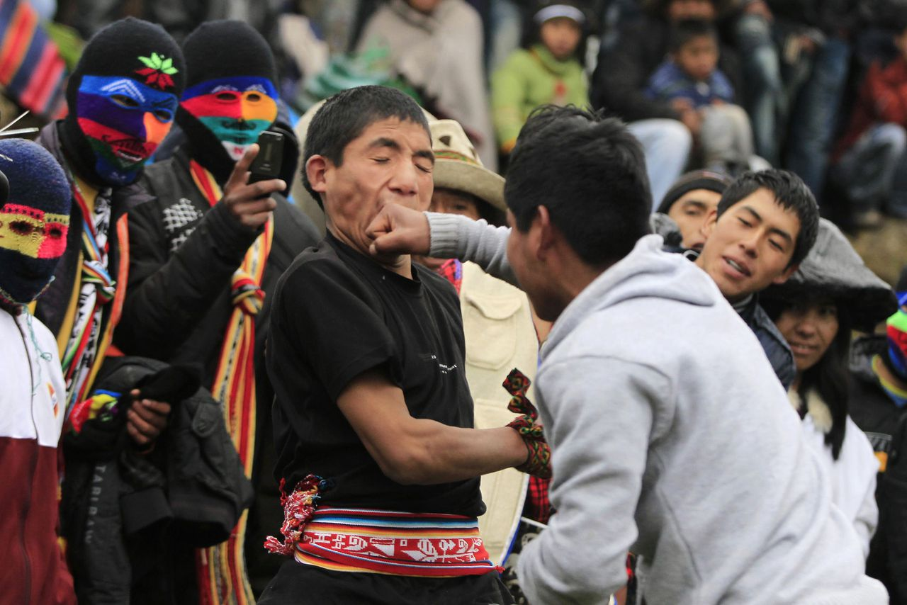 "An Andean man receives a punch during a one-on-one fight during the ""Takanakuy"", a traditional festivity at Chumbivilcas province, in Cuzco, December 25, 2011. ""Takanakuy"", which means ""when the blood is boiling"" in Quechua, is an annual and ancient celebration inherited from the pre-hispanic Chanka culture, that gives hundreds of Andean villagers the chance to solve their love, honour and property problems through the force of blows as a way to put differences behind them before the New Year. Picture taken December 25, 2011. REUTERS/Enrique Castro-Mendivil (PERU - Tags: SOCIETY)"