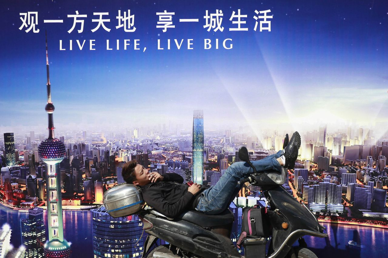 A man rests on a motorcycle in front of an advertisement in central Shanghai in this October 18, 2012 file photo. China's economy is finally regaining traction, official and private sector factory surveys showed on November 1, 2012, although the recovery remains sluggish with the latter recording its 12th straight month of slowing growth. REUTER/Aly Song/Files (CHINA - Tags: BUSINESS SOCIETY)