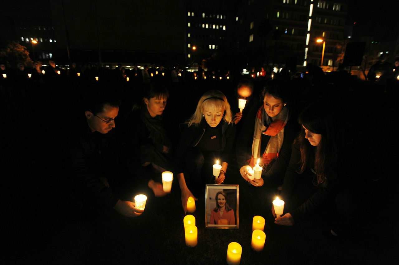 """TUCSON, AZ - JANUARY 8: (L-R) Monty Edmonds, 36, of Tucson, Maggie Kipling, 34, of Tucson, Leigh Harris, 50, of Phoenix, Arizona, Bella Furr, 21, of Tucson and Sarah Herrmann, 22, of Tucson participate in a vigil at University Medical Center for U.S. Rep. Gabrielle Giffords (D-AZ), who was shot during an event in front of a Safeway grocery store January 8, 2011 in Tuscon, Arizona. U.S. Rep. Gabrielle Giffords (D-AZ) was shot in the head at a public event entitled """"Congress on your Corner"""" when a gunman opened fire outside a Safeway grocery store in Tucson, Arizona. It was reported that eighteen people were shot, including members of Giffords' staff, and six are dead, including one young child. One suspect is in custody. Laura Segall/Getty Images/AFP == FOR NEWSPAPERS, INTERNET, TELCOS & TELEVISION USE ONLY =="""