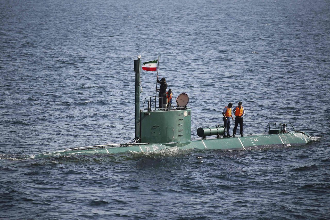 EDITORS' NOTE: Reuters and other foreign media are subject to Iranian restrictions on their ability to film or take pictures in Tehran. Military personnel place a flag on a submarine during the Velayat-90 war games by the Iranian navy in the Strait of Hormuz in southern Iran December 27, 2011. Iran threatened on Tuesday to stop the flow of oil through the Strait of Hormuz if foreign sanctions were imposed on its crude exports over its nuclear ambitions, a move that could trigger military conflict with economies dependent on Gulf oil. REUTERS/IIPA/Ali Mohammadi (IRAN - Tags: POLITICS MILITARY ENERGY TPX IMAGES OF THE DAY)