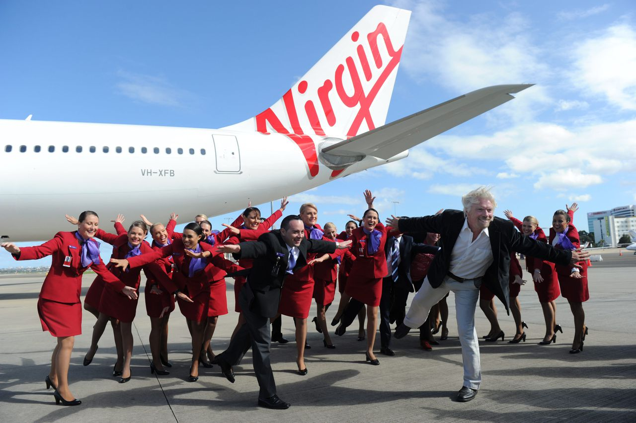 epa02716764 Sir Richard Branson (front R) shows off the new branding for the Virgin Australia airline, replacing Virgin Blue and V Australia brands at Sydney Airport, Sydney, Australia, on 04 May 2011. EPA/DEAN LEWINS AUSTRALIA AND NEW ZEALAND OUT