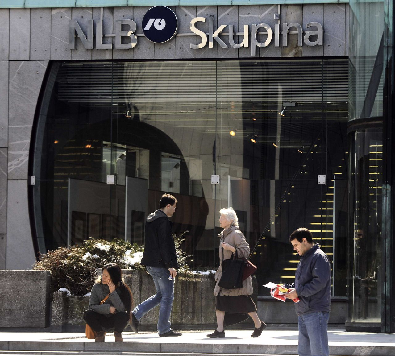 "People walk in front of the Ljubljanska banka building in Ljubljana, March 28, 2013. Cyprus may be a ""special case"" in the eyes of European officials, but their handling of its bailout is taking a toll on another small euro zone member with an over-burdened banking sector - Slovenia. REUTERS/Srdjan Zivulovic (SLOVENIA - Tags: BUSINESS)"