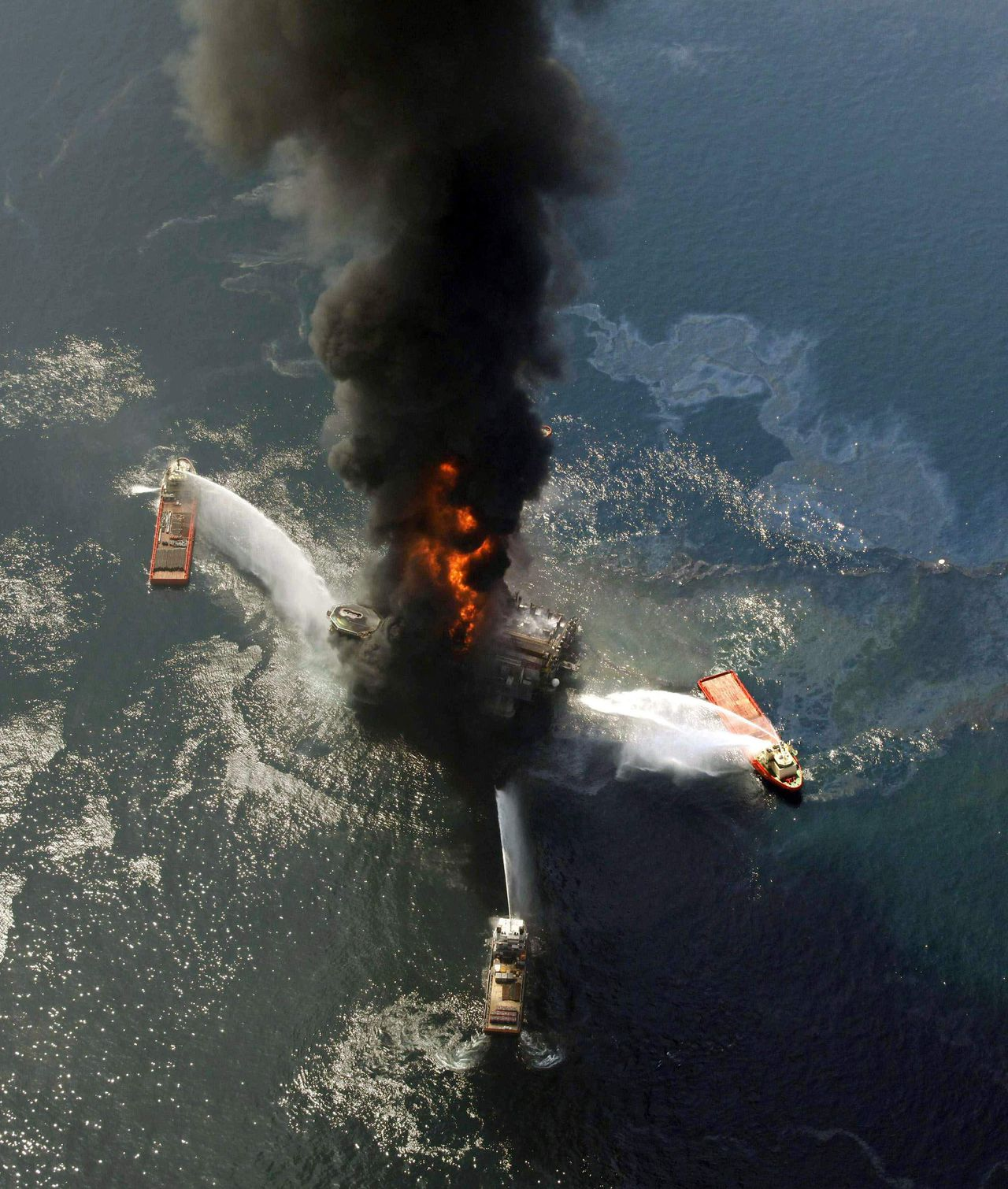 """De brand op 21 april op het olieplatform Deepwater Horizon. Foto AP FILE - This April 21, 2010, file photo show the Deepwater Horizon oil rig burning after an explosion in the Gulf of Mexico, off the southeast tip of Louisiana. In yet another failed attempt, this time called """"Top Kill"""", a high-tech nation threw brute mass, old tools and golf balls at the oil gushing from the ocean floor, like blast from past. (AP Photo/Gerald Herbert, File)"""