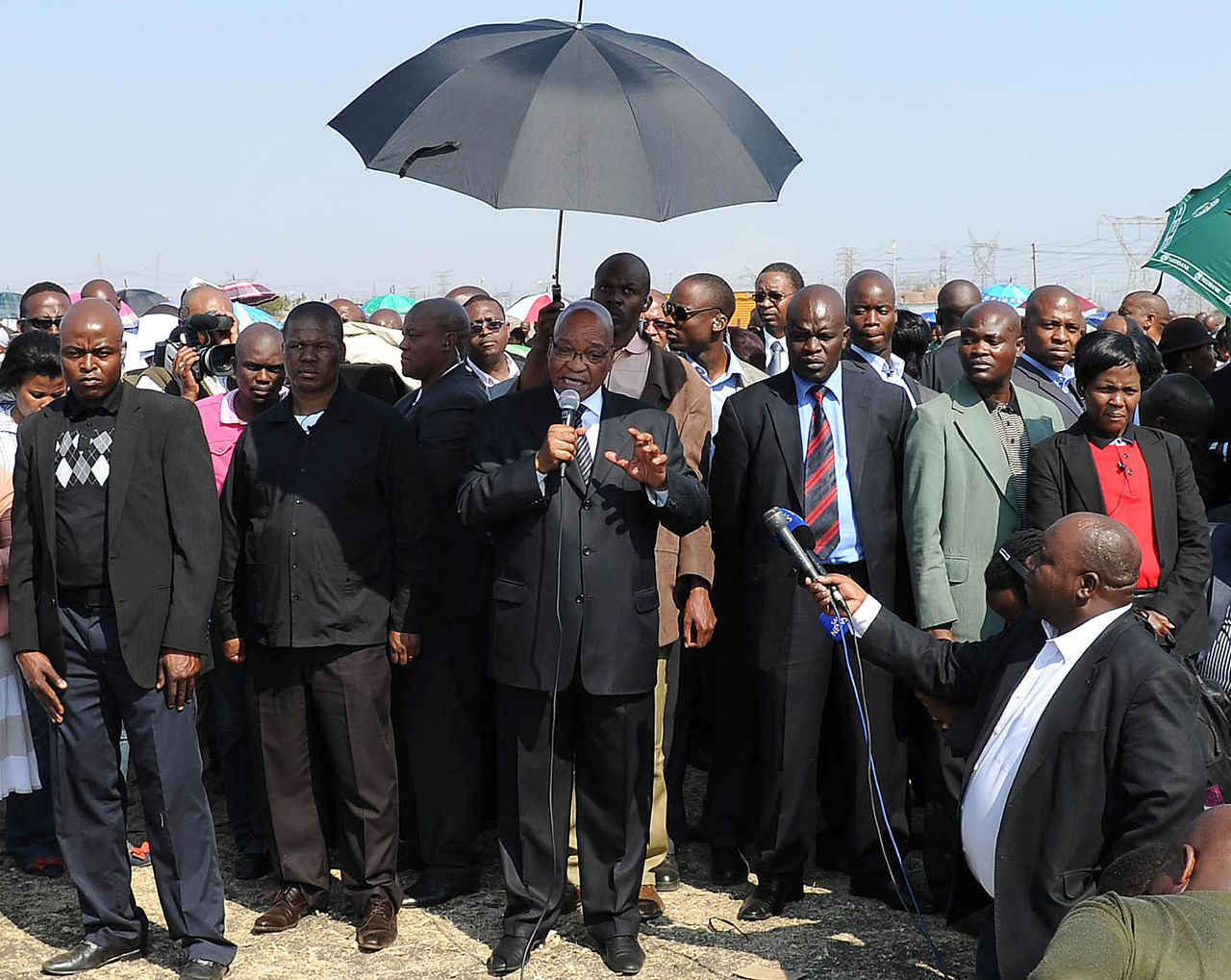 South African president Jacob Zuma (C) speaks to the striking platinum miners on August 22, 2012 at London-listed Lonmin's Marikana platinum mine, where police opened fire on hundreds of workers staging a wildcat strike on August 16, that left 44 dead. The 44 deaths at Lonmin's Marikana mine last week have forced South Africa to confront a culture of violence that runs from the country's gruesome crimes to the language of its politics, experts said. AFP PHOTO / STR