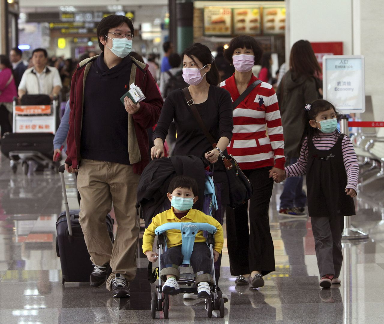 Tourists wear masks at the Songshan Airport in Taipei, Taiwan, Saturday, April 27, 2013. Taiwan confirmed its first case of a new deadly strain of bird flu. The Centers for Disease Control said Wednesday that a 53-year-old man became ill with fever after returning from a visit to the eastern Chinese province of Jiangsu on April 9. He twice tested negative for H7N9 but eventually tested positive Wednesday after his condition deteriorated, CDC official Chang Feng-yi said. (AP Photo/Chiang Ying-ying)