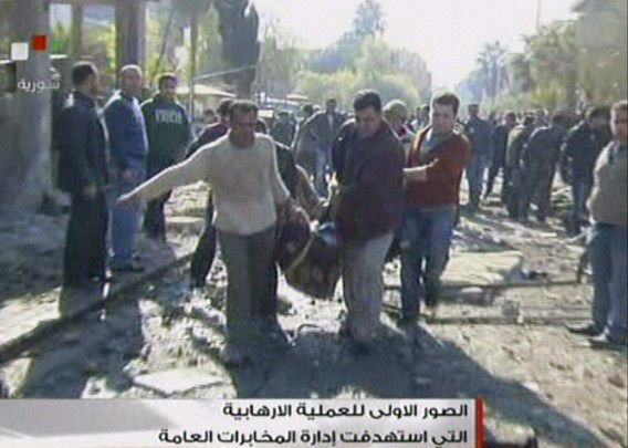 "An image grab taken from Syrian state TV on December 23, 2011 shows Syrians carry away a dead body at the site of a suicide attack outside a security service base in Damascus on December 23, 2011. Suicide bombers hit two security service bases in Damascus killing many civilians and some soldiers, state television reported, in the first attacks of their kind in a quarter of a century. AFP PHOTO/HO/SYRIAN TV RESTRICTED TO EDITORIAL USE - MANDATORY CREDIT ""AFP PHOTO / SYRIAN TV"" - NO MARKETING NO ADVERTISING CAMPAIGNS - DISTRIBUTED AS A SERVICE TO CLIENTS"