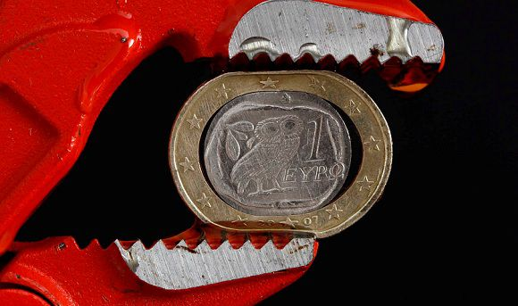 Caption: A Greek one Euro coin is squeezed by the teeth of a pair of grips in this photo illustration taken in Athens, October 20, 2011. A national unity government aiming to save Greece from bankruptcy is set to win a parliamentary vote of confidence on November 16, 2011, but the leader of the conservative faction gave only qualified support. Photo illustration taken October 20, 2011. REUTERS/Yiorgos Karahalis/Files (GREECE - Tages: - Tags: BUSINESS POLITICS)