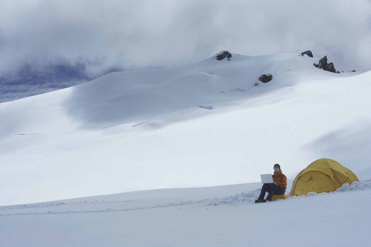 Hiker using laptop outside of tent on snowy mountain peak --- Image by © Garry Moore/moodboard/Corbis