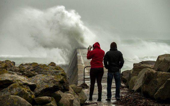 Zee slaat over de pier in Esquibien, het westen van Bretagne, Frankrijk. De wind aan de kust bereikte snelheden van wel 100 km per uur.