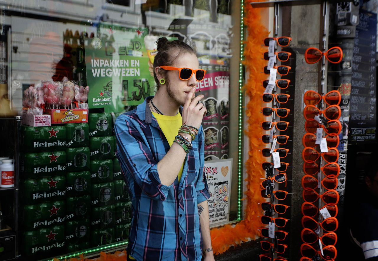 A man smokes near a shop selling orange sunglasses in Amsterdam April 29, 2013. The Netherlands is preparing for Queen's Day on April 30, which will also mark the abdication of Queen Beatrix and the investiture of her eldest son Willem-Alexander. REUTERS/Kevin Coombs (NETHERLANDS - Tags: ROYALS ENTERTAINMENT POLITICS)