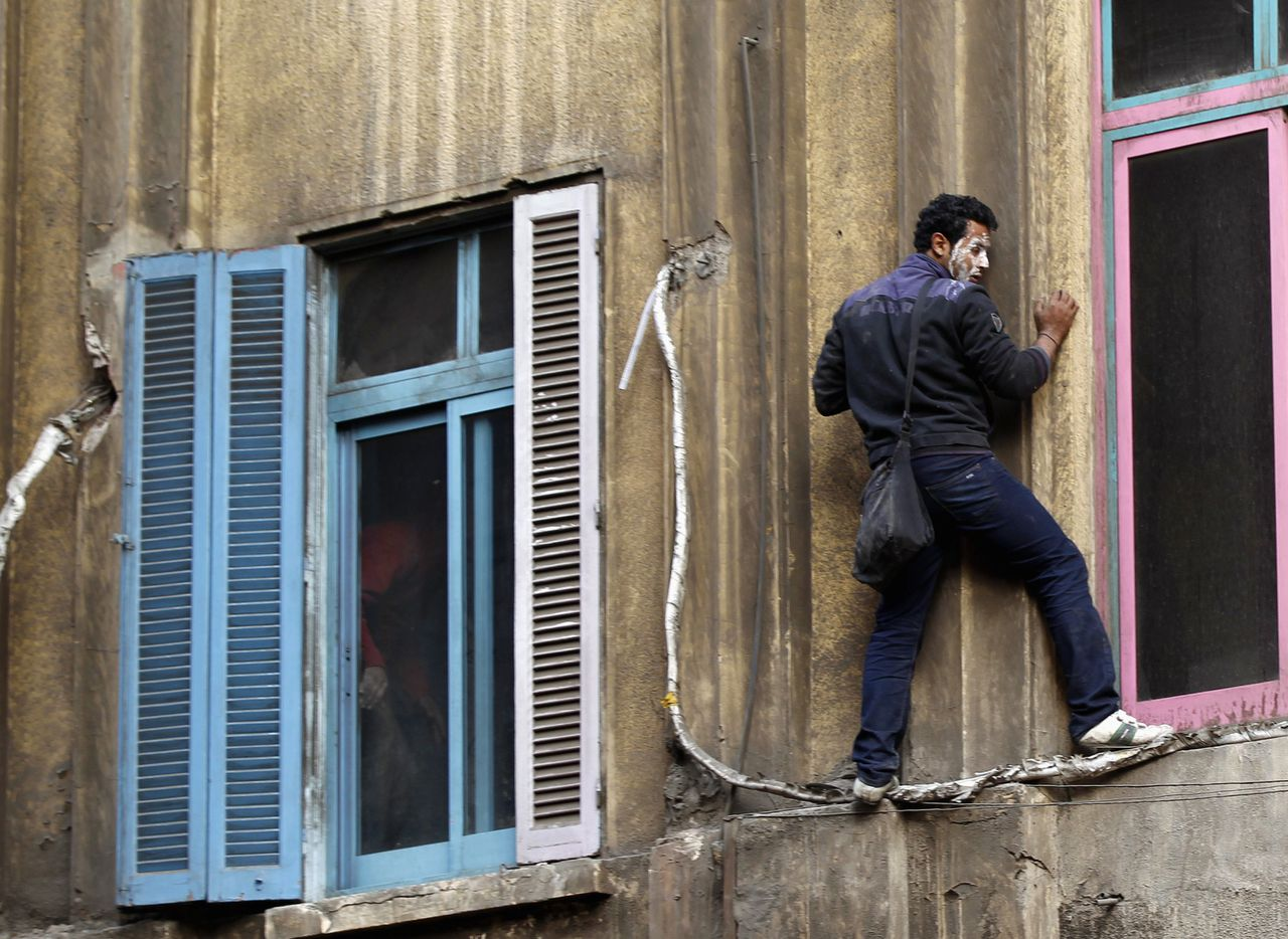 A protester climbs a burned building to rescue residents trapped by fire, during clashes with police in Cairo November 21, 2011. REUTERS/Goran Tomasevic (EGYPT - Tags: POLITICS CIVIL UNREST)