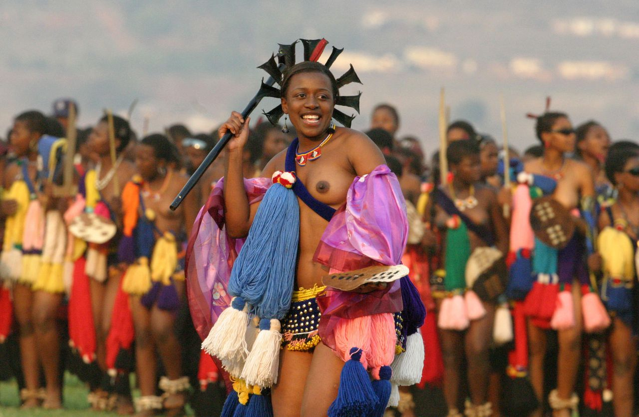 De duizenden maagden dansen de traditionele vruchtbaarheidsdans voor koning Mswati III van Swaziland.Foto AFP ==== Leader of the maidens dances in front of King Mswati III and his delegates during an annual traditional reed dance at Ludzidzini palace outside the capital Mbabanein on September 1, 2008. The final day of the annual dance attracted a record 70,000 girls, some of them as young as six years of age. The ceremony has a more serious mission -- to draw attention to AIDS and encourage abstinence among young women, in a small southern African nation ravaged by AIDS and poverty. AFP PHOTO/PABALLO THEKISO