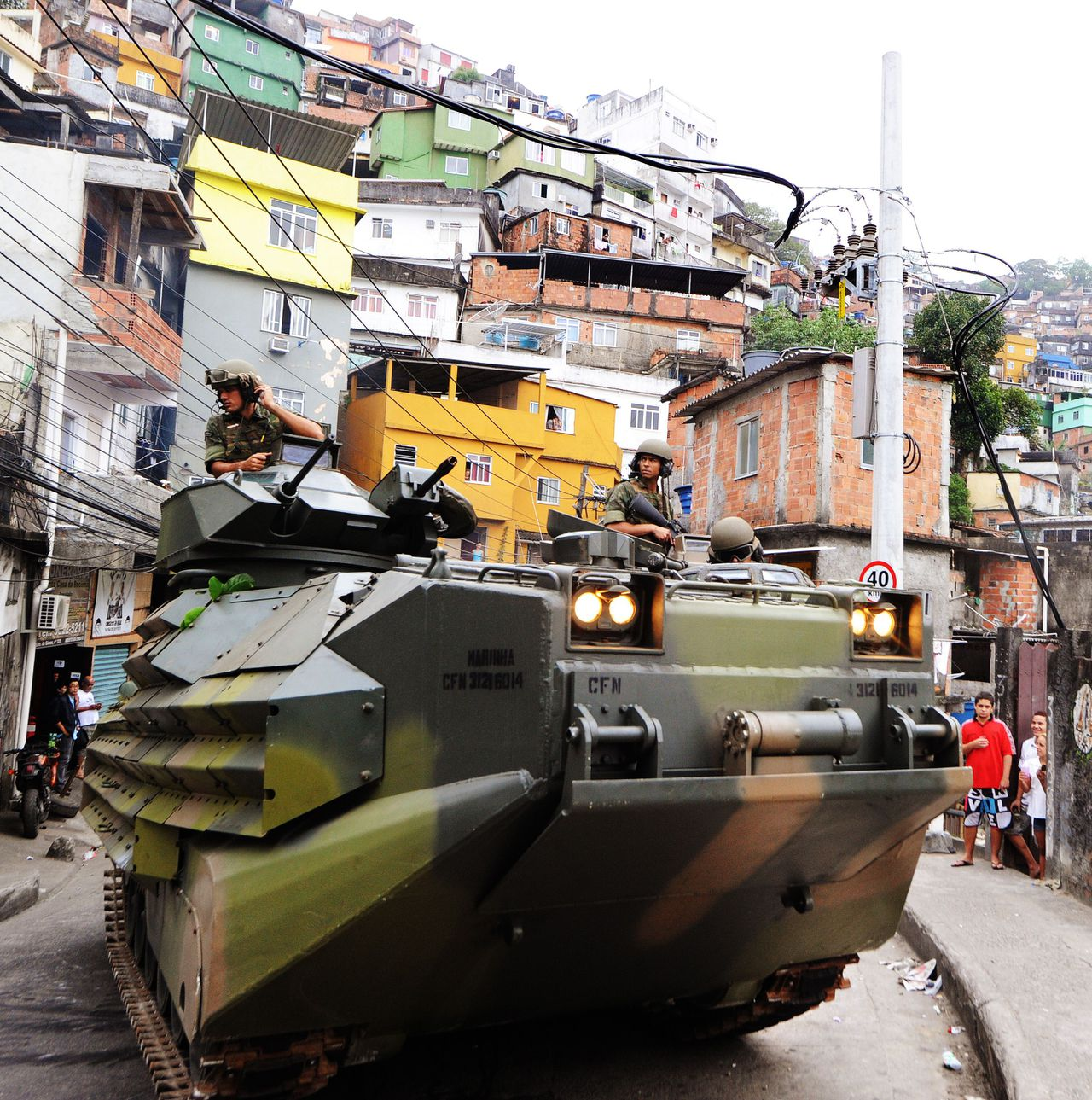 Brazilian marines on an amphibious assault vehicle (AAV) drive along a street of the Rocinha shantytown in Rio de Janeiro, Brazil, on November 13, 2011. Security forces backed by armor and helicopters peacefully seized control of Rio's largest favela early Sunday in a major assault to expel narcotraffickers who had been ruling the area for 30 years. AFP PHOTO ANTONIO SCORZA