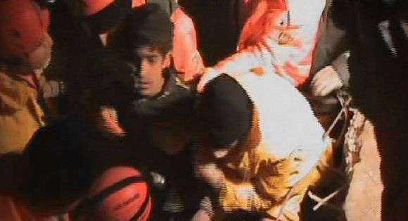 Caption: In this image taken from a video footage by Anatolia, rescuers pull Ferhat Tokay, 13, center left, from the rubble of a collapsed building in Ercis, Van, Turkey, early Friday, Oct. 28, 2011. Rescuers, working under floodlights, pulled the 13-year-old boy alive from the rubble of the collapsed apartment building 108 hours after Sunday's earthquake that hit eastern Turkey. (AP Photo/Anatolia via APTN) EDITORIAL USE ONLY, TURKEY OUT, ROJ TV OUT, TV OUT