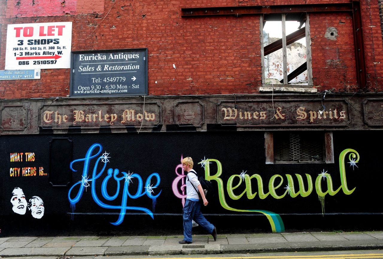A pedestrian walks past a wall covered in graffiti, and which reads 'Hope & Renewal' on a building in Dublin, Ireland, on Sunday, Nov. 13, 2011. German Chancellor Angela Merkel said it's time to embrace a 'political union' in Europe to send a message to bondholders that euro-area leaders are serious about ending the sovereign debt crisis. Photographer: Aidan Crawley/Bloomberg