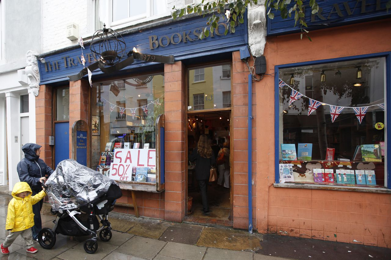 A woman and child walk past The Travel Bookshop in London's Notting Hill area, which is holding a two week closing down sale, Tuesday, Aug., 23, 2011. The bookshop helped inspire and featured in the film Notting Hill, staring Hugh Grant and Julia Roberts. (AP Photo/Alastair Grant)