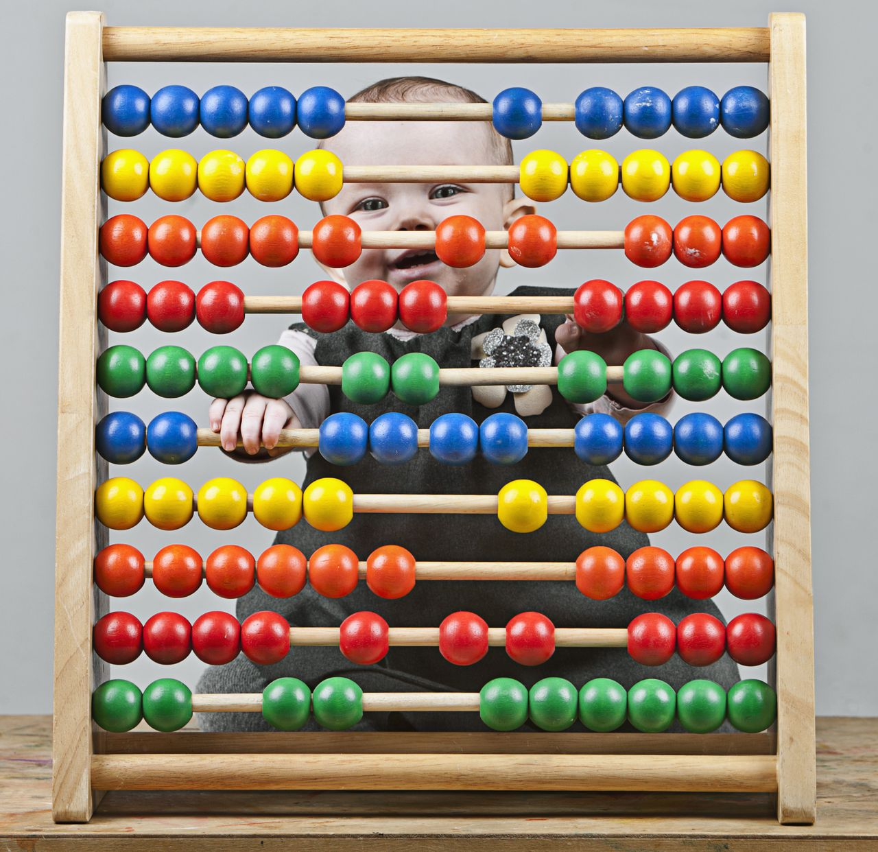 Baby Girl behind Wooden Abacus --- Image by © Justin Paget/Corbis