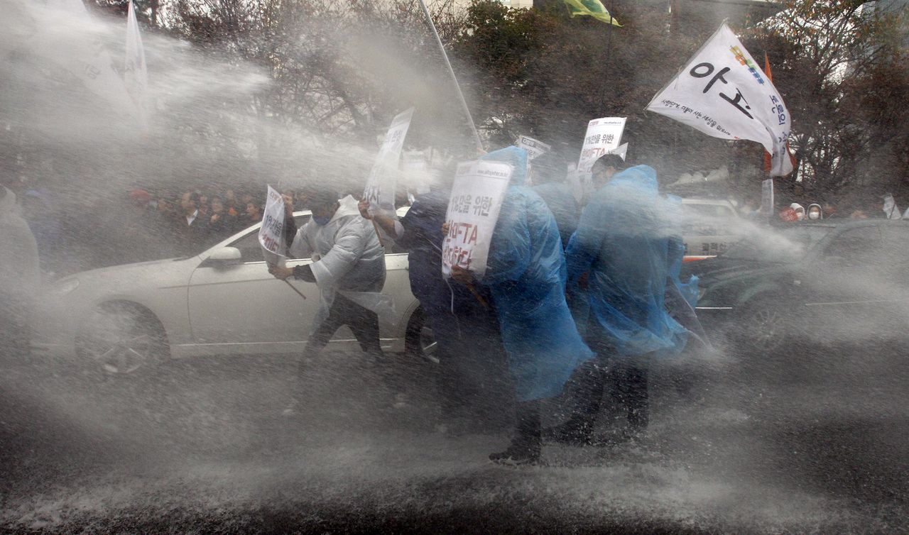 """South Korean protesters are sprayed with water by riot police during a rally against a Free Trade Agreement (FTA) between South Korea and the United States near the National Assembly in Seoul, South Korea, Thursday, Nov. 10, 2011. South Korea's ruling and opposition parties have so far failed to agree on the deal even though the U.S. Congress ratified it last month. The Korean read """" Oppose, the Free Trade Agreement (FTA) between South Korea and the United States."""" (AP Photo/Lee Jin-man)"""