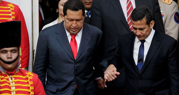 Caption: Venezuela's President Hugo Chavez, left, is aided by Peru's President-elect Ollanta Humala to walk down stairs upon Humala's visit to Miraflores presidential palace in Caracas, Venezuela, Friday, July 15, 2011. Chavez announced Friday he will return to Cuba Saturday to begin a new phase of cancer treatment that will include chemotherapy. (AP Photo/Ariana Cubillos)