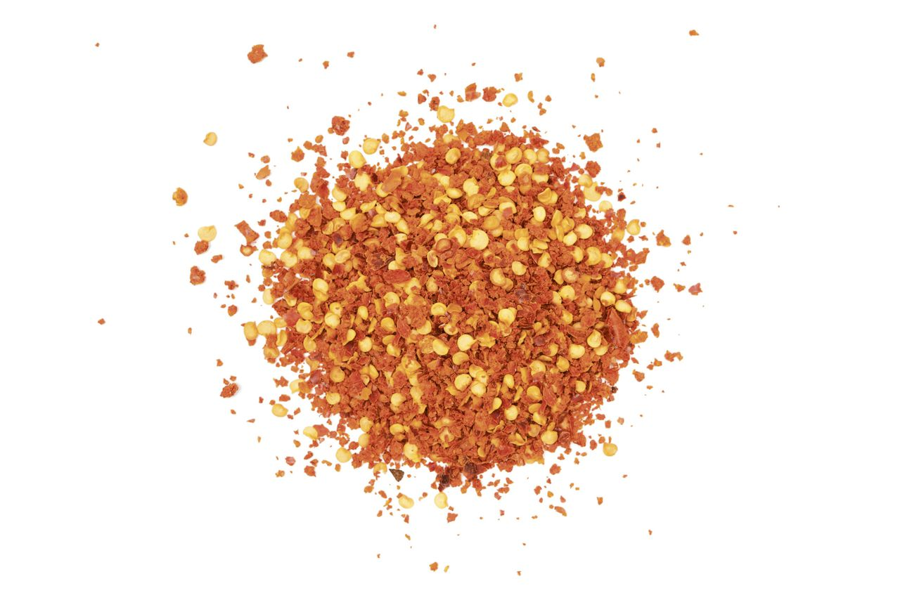 Pile of red hot chili flakes isolated on a white background.