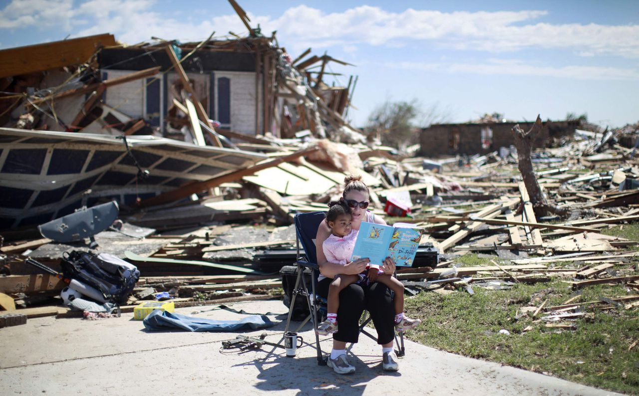 REFILE - CORRECTING TYPO IN BOOK AUTHOR Sarah Dick reads a Doctor Seuss book to her three-year-old daughter Jadyn at the driveway of her tornado-destroyed house in Oklahoma City, Oklahoma May 22, 2013. Rescue workers with sniffer dogs picked through the ruins on Wednesday to ensure no survivors remained buried after a deadly tornado left thousands homeless and trying to salvage what was left of their belongings. REUTERS/Rick Wilking (UNITED STATES - Tags: DISASTER ENVIRONMENT TPX IMAGES OF THE DAY)