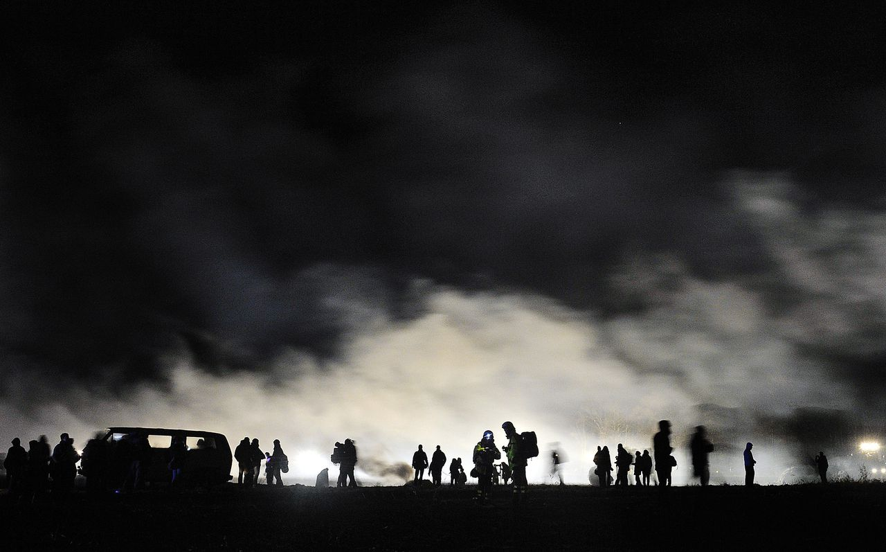 Anti nuclear protesters stand near smoke from fire on a field in Laase, northern Germany, Monday, Nov. 28, 2011. Containers with nuclear waste to from France are on their final stage to to the final storage place in nearby Gorleben. (AP Photo/dapd, Sascha Schuermann)