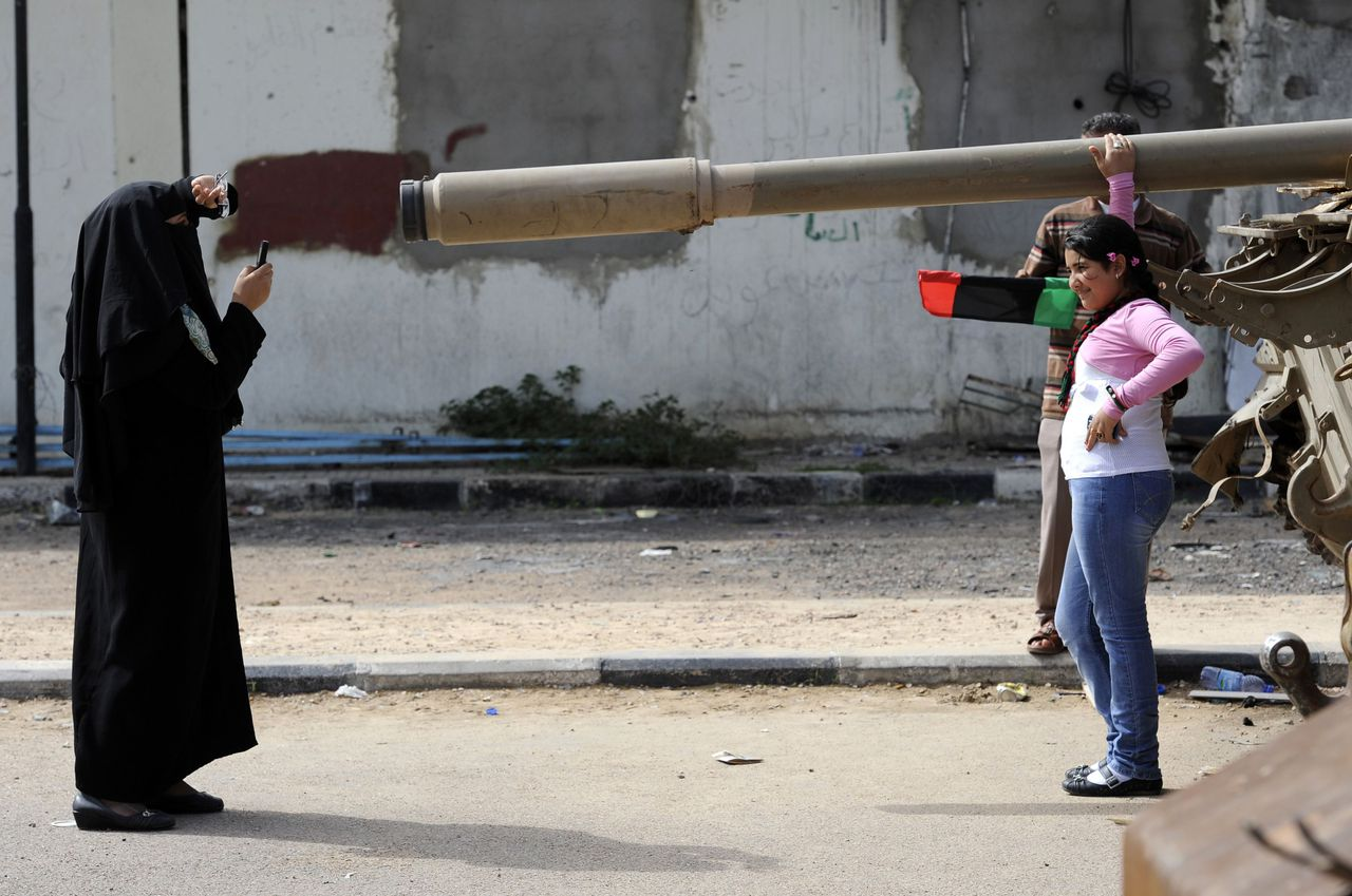 A Libyan woman takes pictures of her daughter in front of a tank as weapons and other items belonging to the former regime are displayed in Misrata on October 23, 2011. Libya's new leaders will declare liberation in the wake of Moamer Kadhafi's death, paving the way for the formation of an interim government followed by the first free vote in 42 years. AFP PHOTO/PHILIPPE DESMAZES