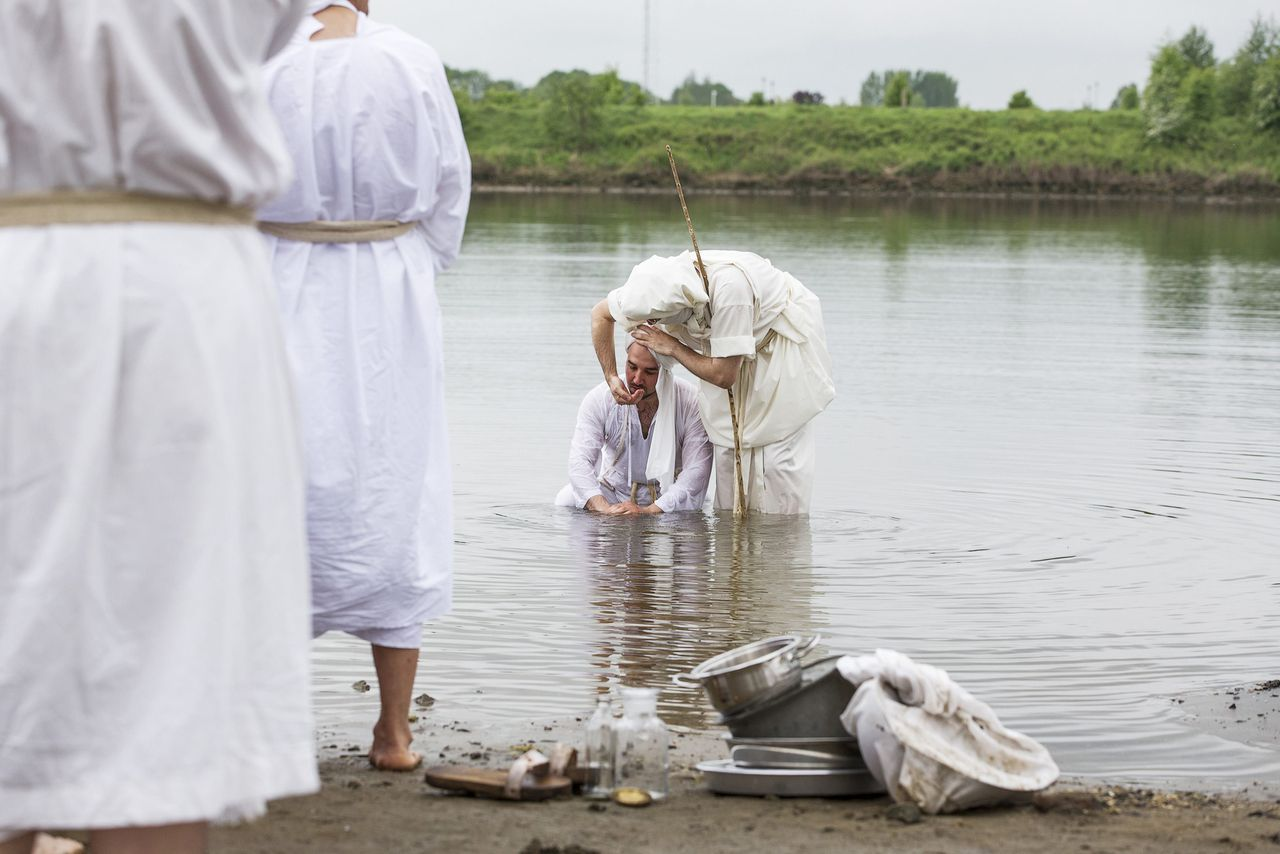 A priest (R) splashes water at a believer during a baptising ceremony for Mandaen followers at the Lek River near Houten May 20, 2013. May 20 is a holy day for the Mandaeans all over the world as followers cleanse themselves by being baptised in a river of choice. The Mandaeans, also known as the Sabeans, are a monotheistic and pacifistic religious community who are recognized as followers of John the Baptist. The Mandaeans, which once numbered about 30,000 and lived mostly in southern Iraq, have fled all over the world due to religious persecution. REUTERS/Michael Kooren (NETHERLANDS - Tags: RELIGION SOCIETY TPX IMAGES OF THE DAY)