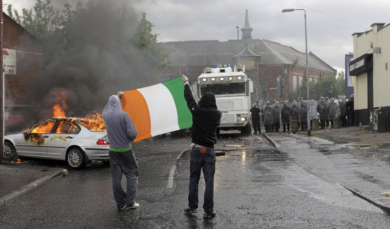 Nationalist rioters hold the Irish flag as they face riot police in the Ardoyne area of North Belfast, Northen Ireland, Thursday, July 12, 2012. Trouble broke out after an Orange Order march passed the area. The Twelfth of July is the busiest day of the marching season in Northern Ireland with thousands of Orangemen and women, accompanied by marching bands, taking part in hundreds of parades. The Orange Order holds its main Belfast event, which commemorates King William III's 1690 Battle of the Boyne victory over Catholic King James II. (AP Photo/Peter Morrison)