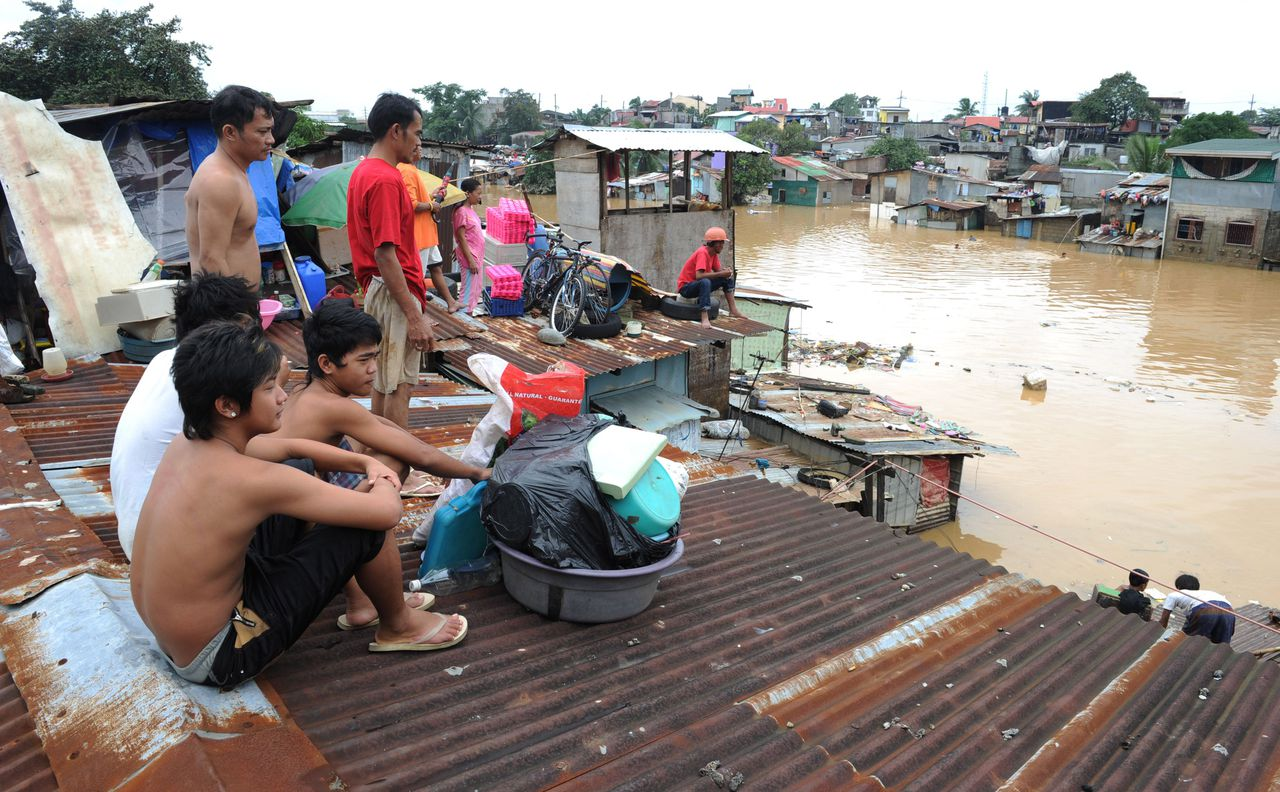 People take refuge on their rooftops in a suburb of Manila on August 9, 2012. Philippine authorities appealed on August 9 for help in getting relief to two million people affected by deadly floods in and around the capital, warning that evacuation centres were overwhelmed. AFP PHOTO / Jay DIRECTO