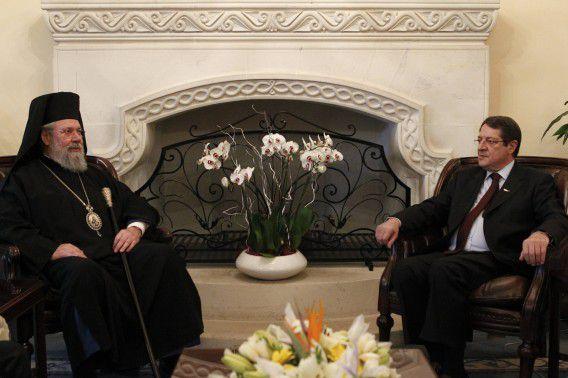 De Cypriotische president Nicos Anastasiades tijdens een gesprek met aartsbisschop Chrysostomos van de orthodoxe kerk. De kerk is bereid te investeren in staatsobligaties om te helpen de financiële nood van het land te lenigen.